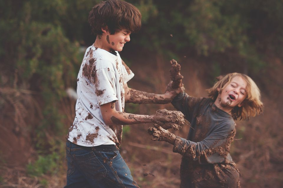 Young boys playing in mud