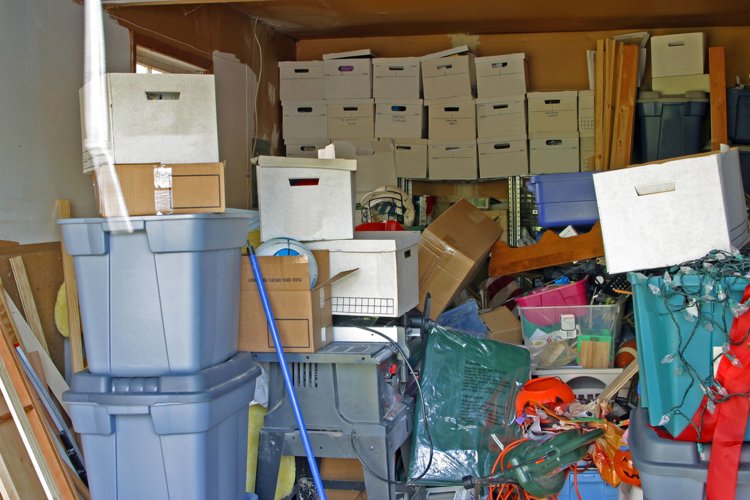 Garage full of clutter including boxes and Christmas lights.