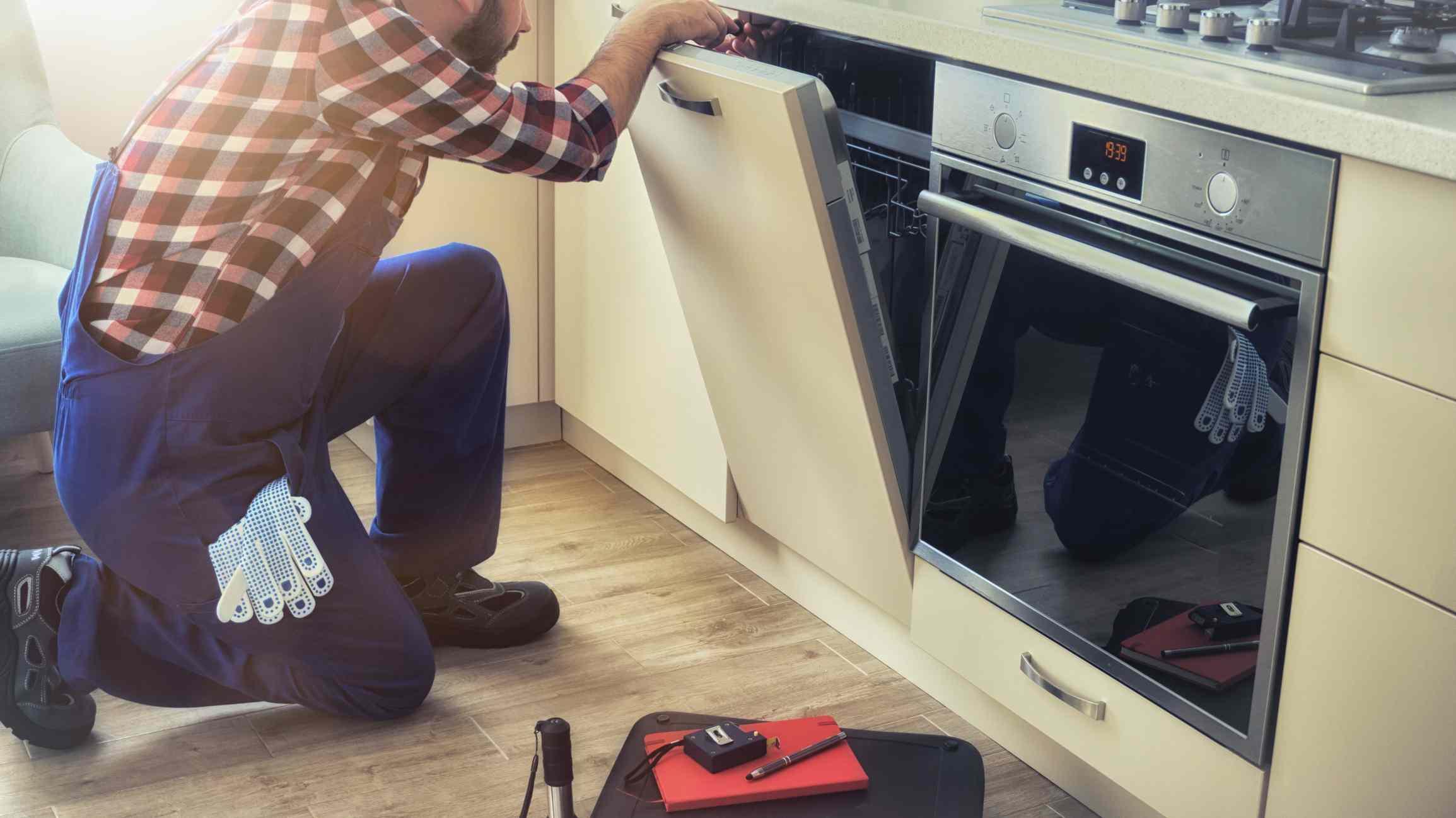 Hombre de servicio arreglando la máquina lavaplatos en la cocina de su casa