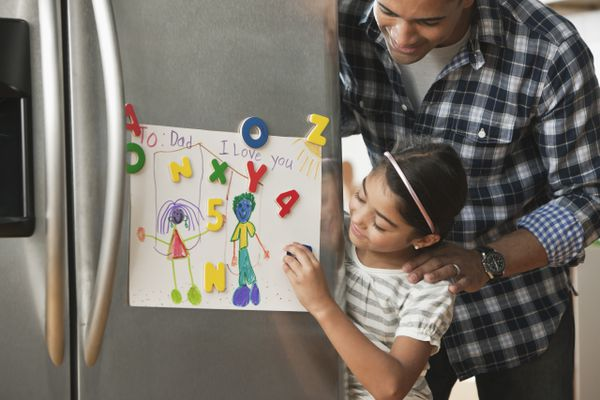 Father looking at daughter's artwork on refrigerator