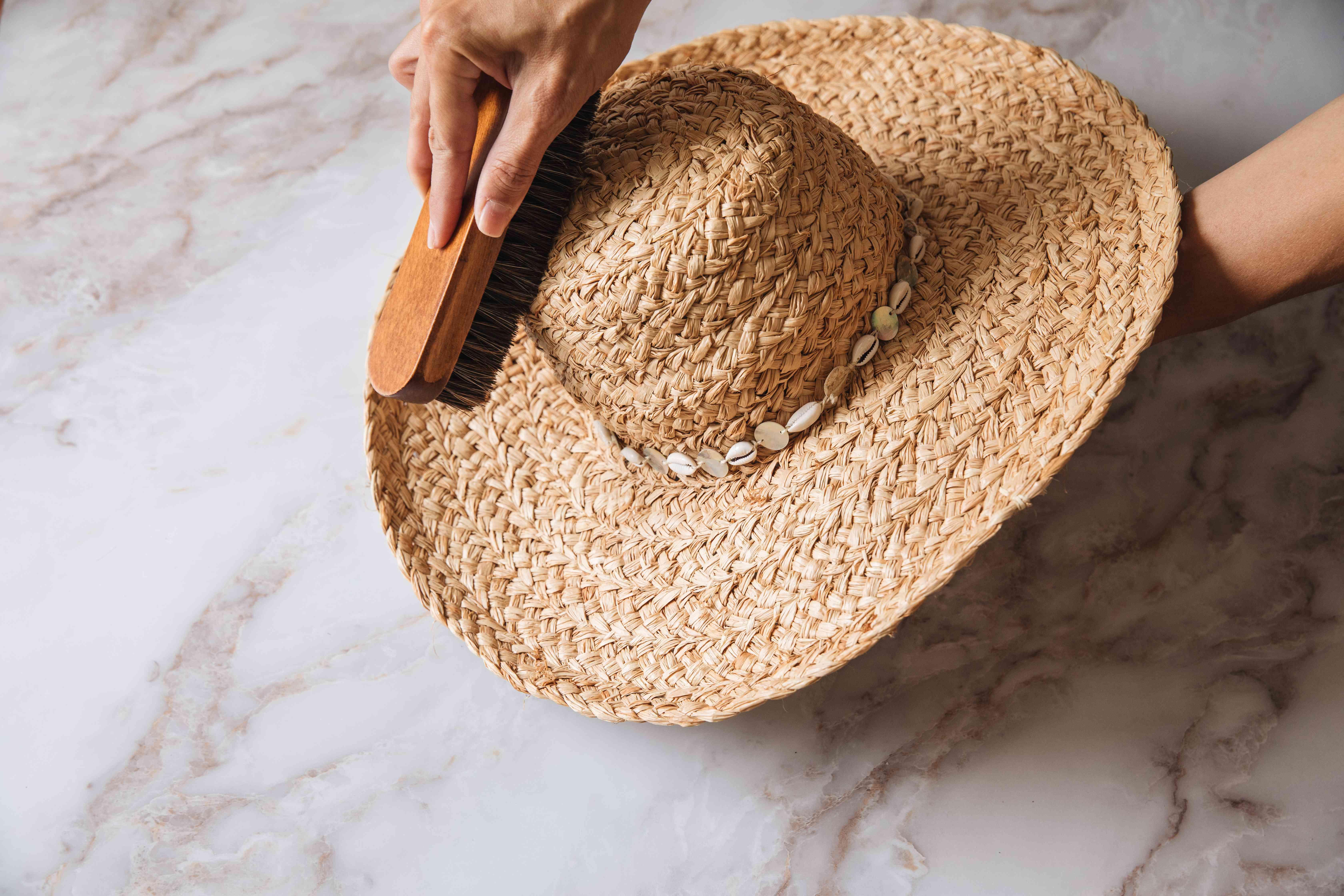 Someone brushing a straw hat