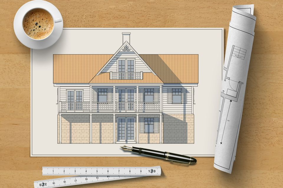 Architectural elevation drawing of a wooden house on a table with pen, ruler, rolled-up blueprint, and cup of coffee