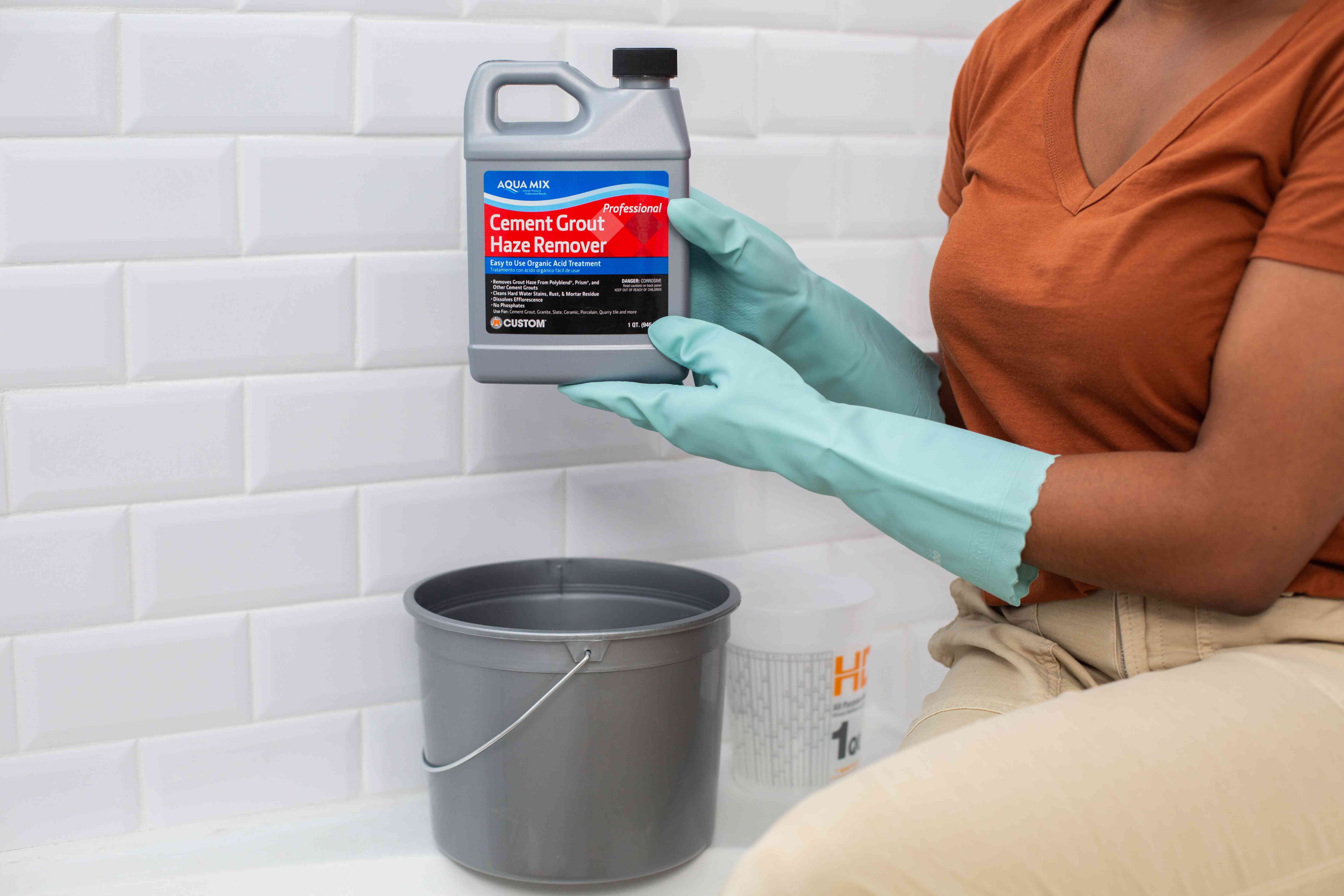 Grout haze remover bottle held over gray bucket with teal latex gloves