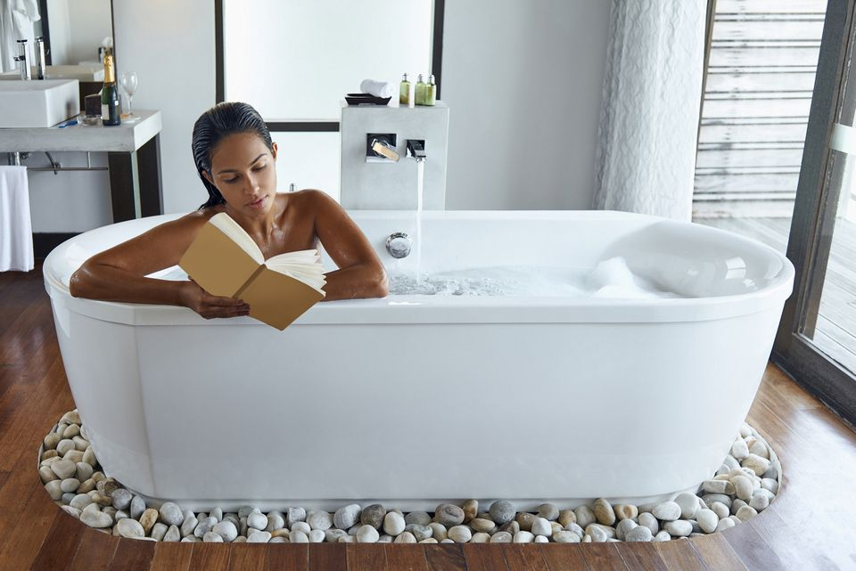 woman reading while taking bath