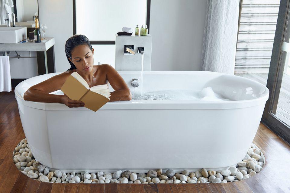 woman reading while taking bath