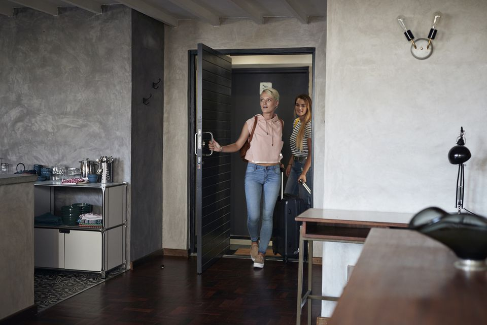 two young women entering a modern apartment
