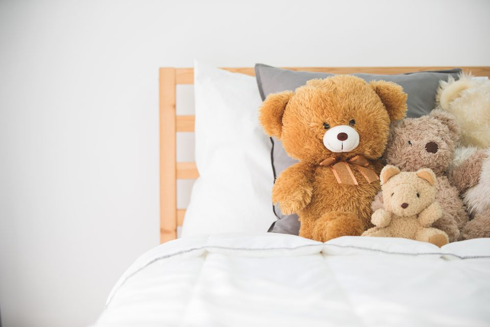 Cute teddy bears in kids white room.