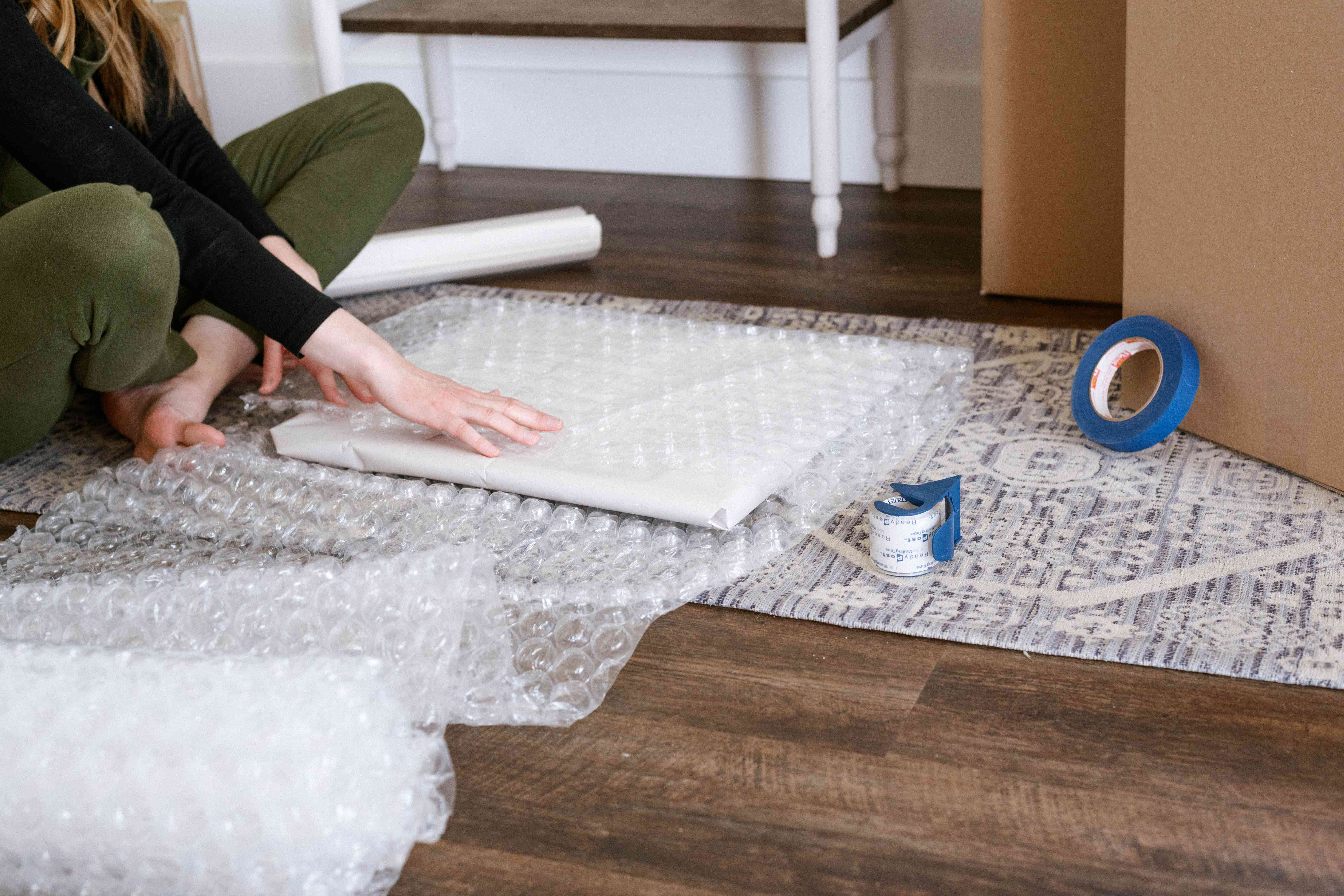 person putting bubble wrap on artwork