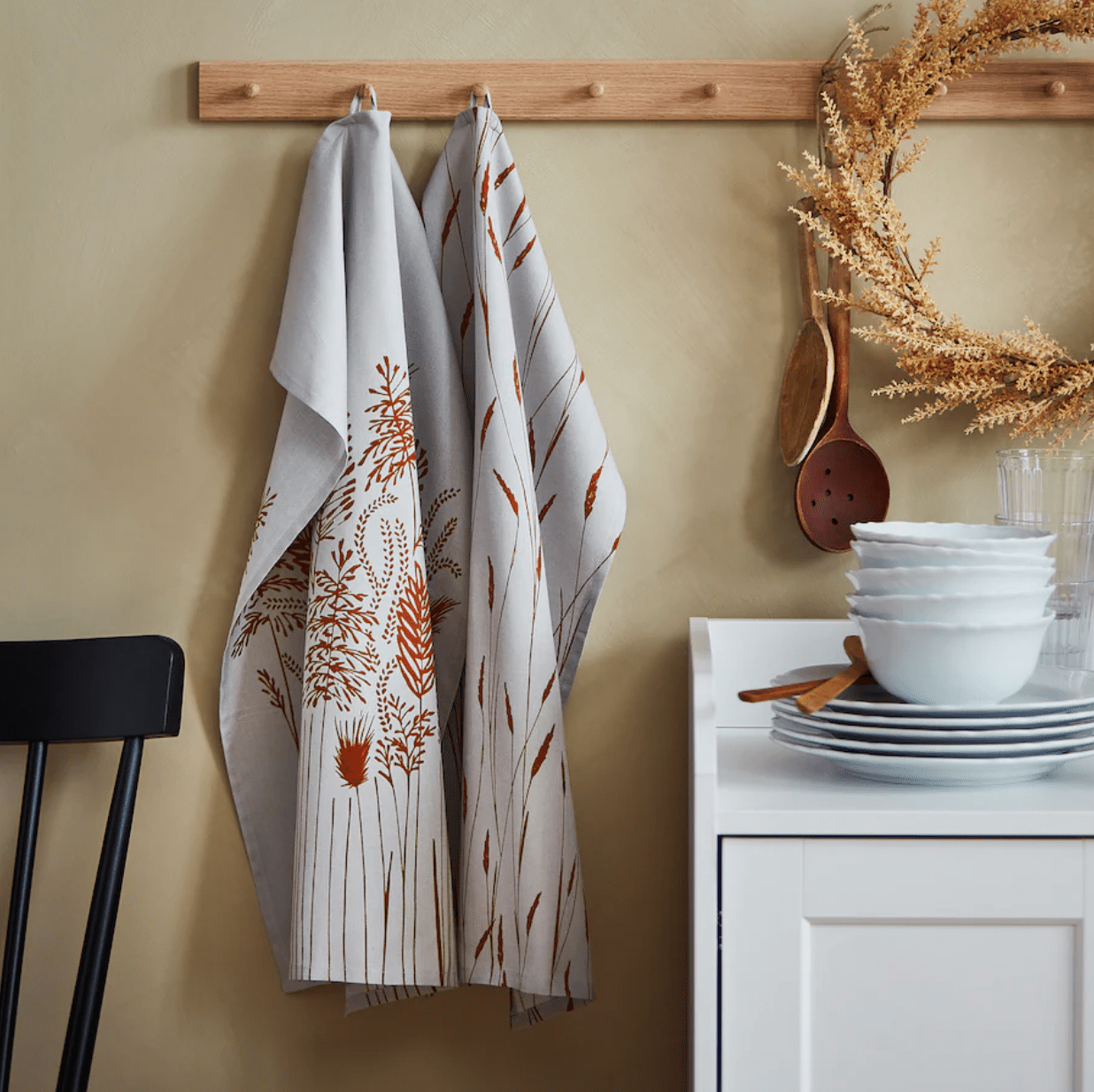Two grey and red dish towels hanging on pegs