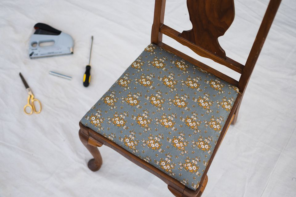 Wooden chair with new printed upholstery on white sheet with materials and tools
