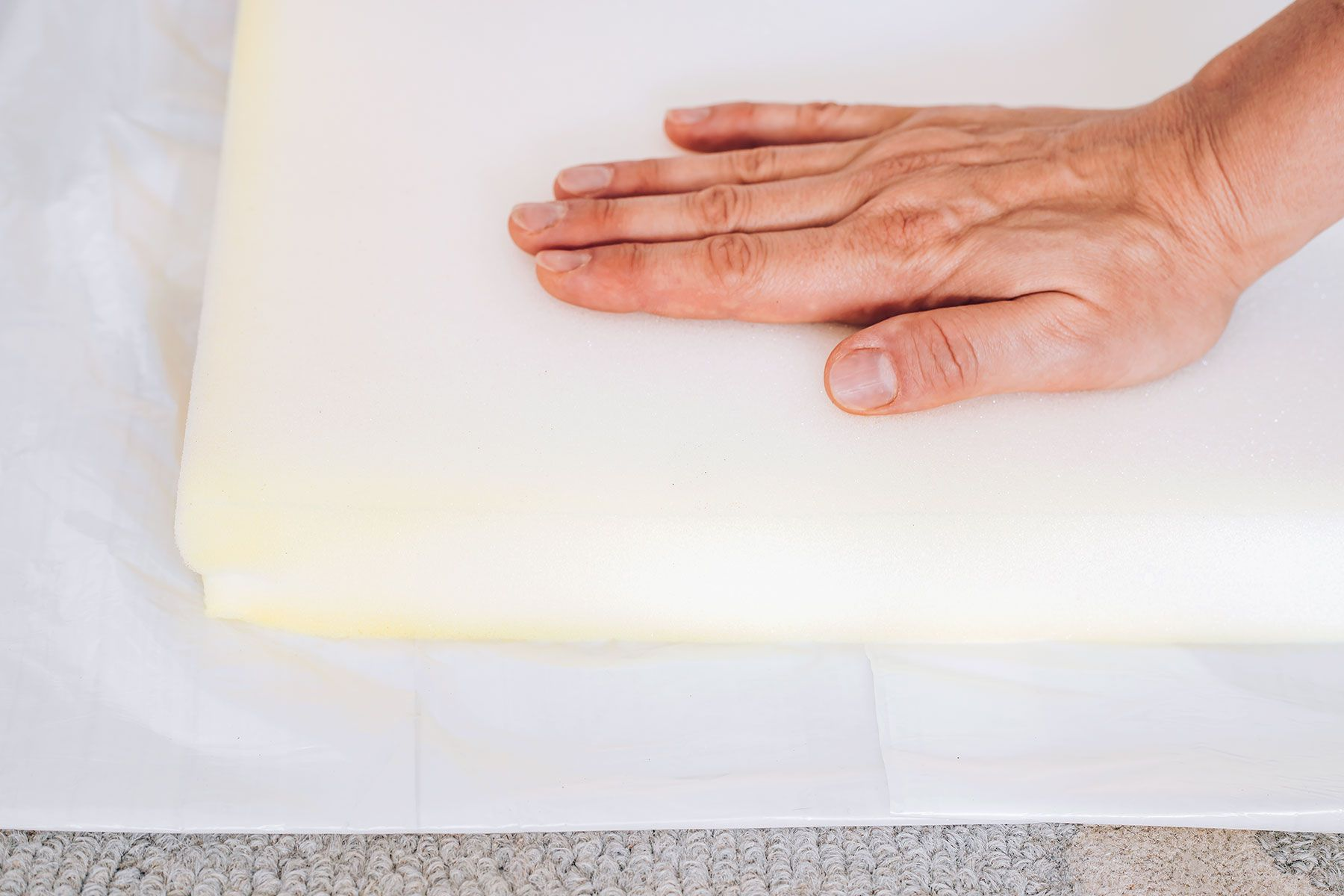 Foam mattress pad removed from bed topper and placed on white tarp