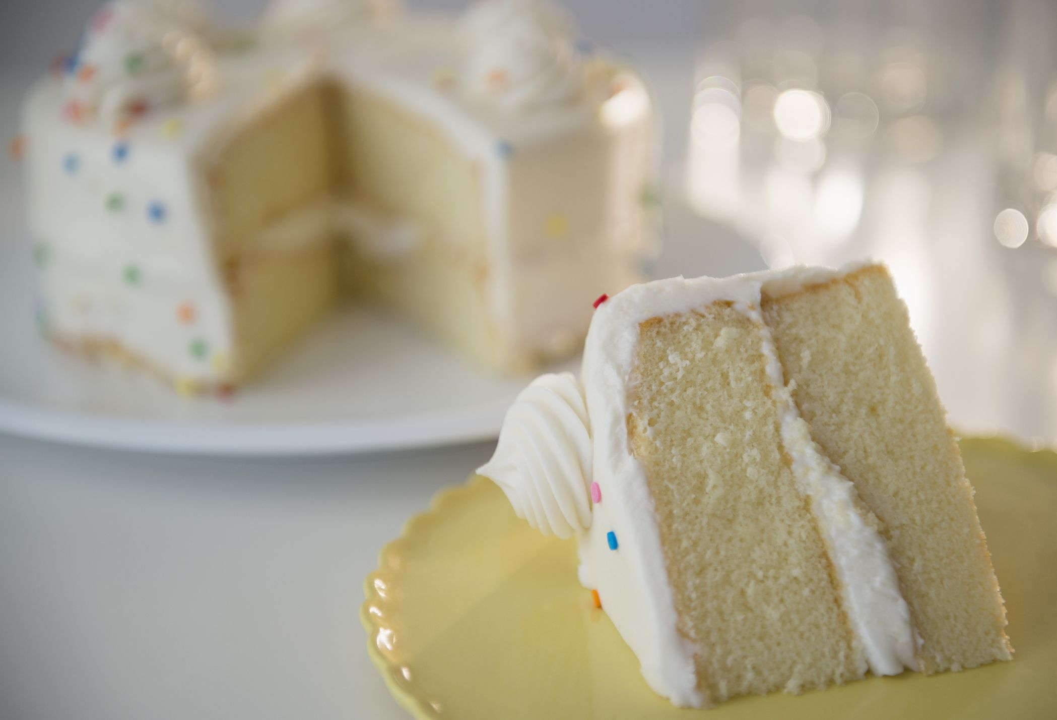 A slice of angel food cake with funfetti icing.