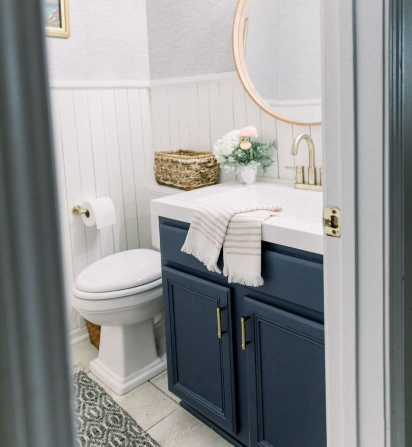 Updated powder room with shiplap on walls and dark blue vanity.