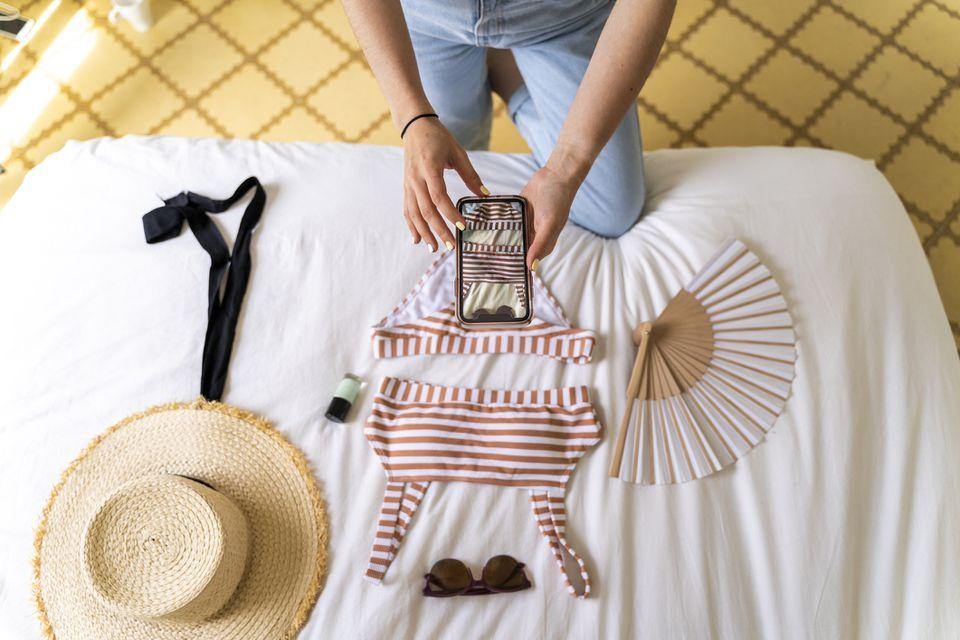 Woman taking smartphone picture of bikini on bed