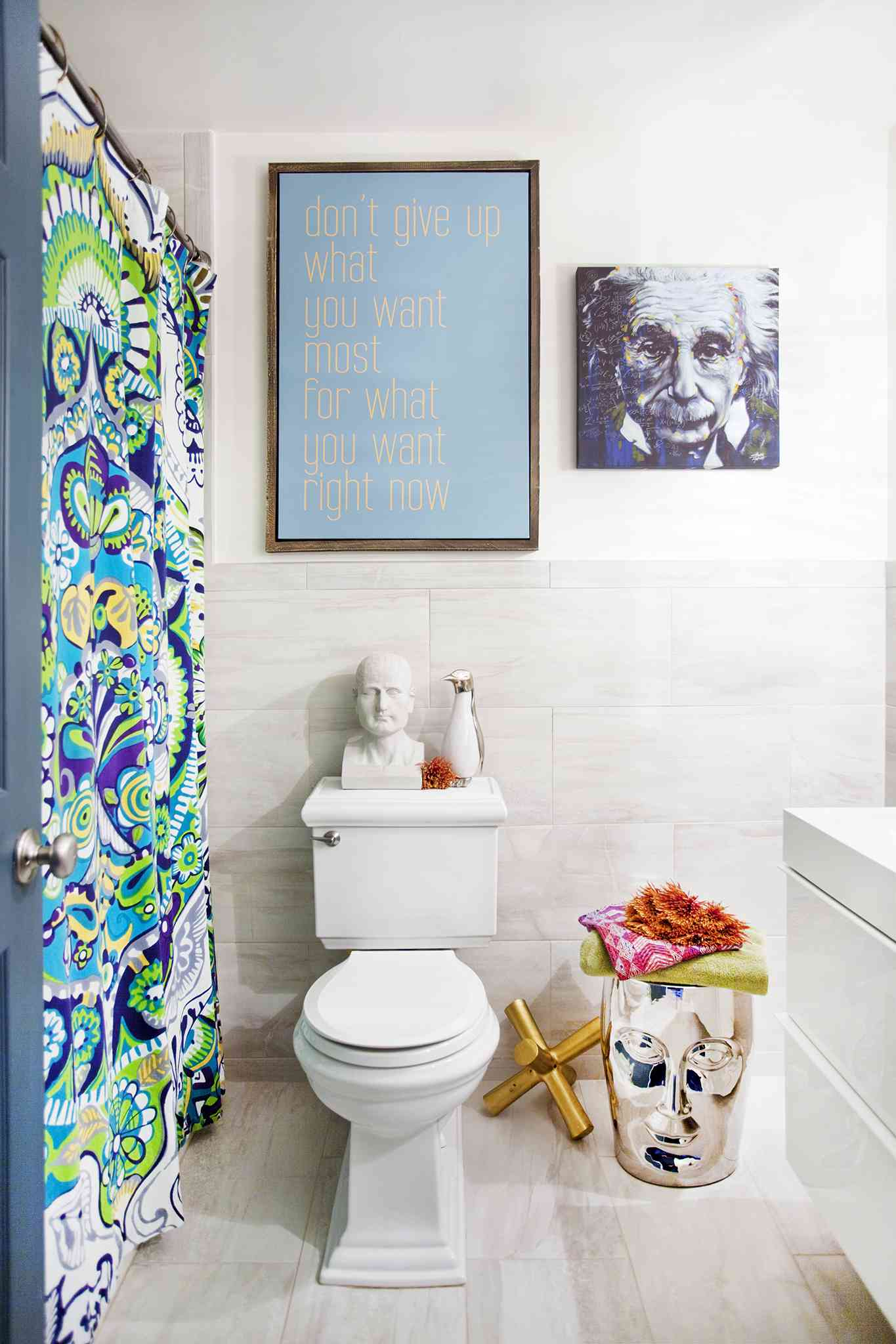 Beth Diana Smith's primary bathroom features a colorful shower curtain and unique art