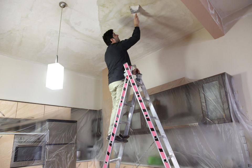 Man working on the ceiling of a kitchen
