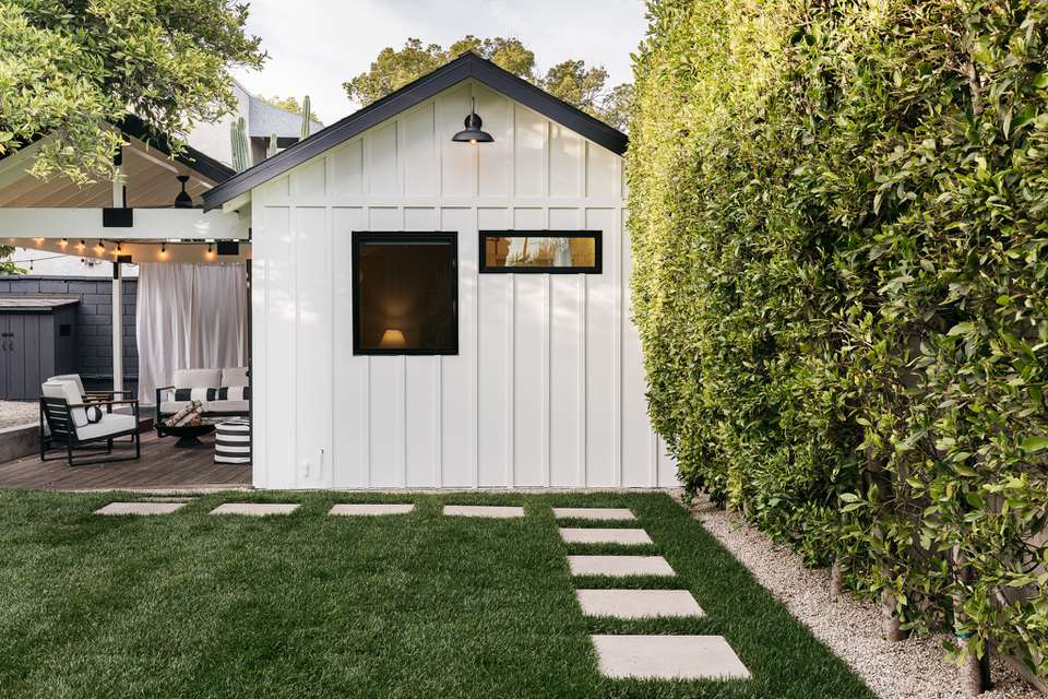 Backyard with a privacy fence made with shrubs next to white shed and pathway in grass