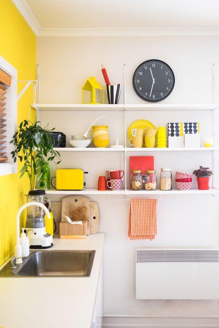 Estantería de cocina blanca con platos amarillos, tazas y un reloj negro. almacenamiento