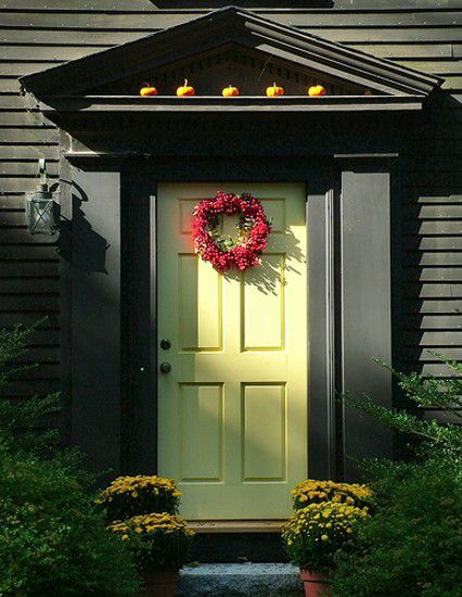 Yellow front door with fall decor