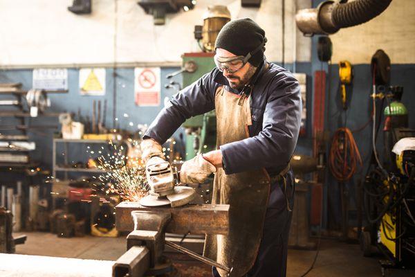 man using grinder in workshop