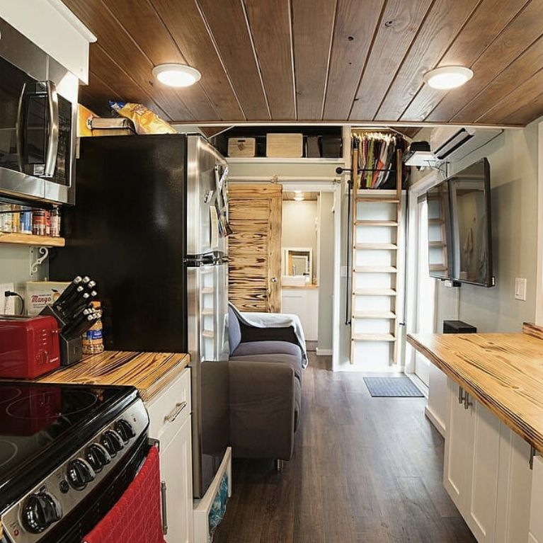 a tiny house kitchen with wood cabinets and full size appliances