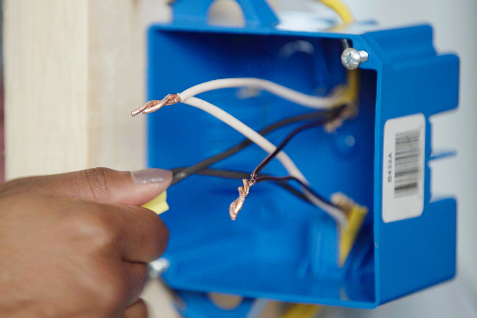 Bare copper ground wires joined together in blue electrical junction box