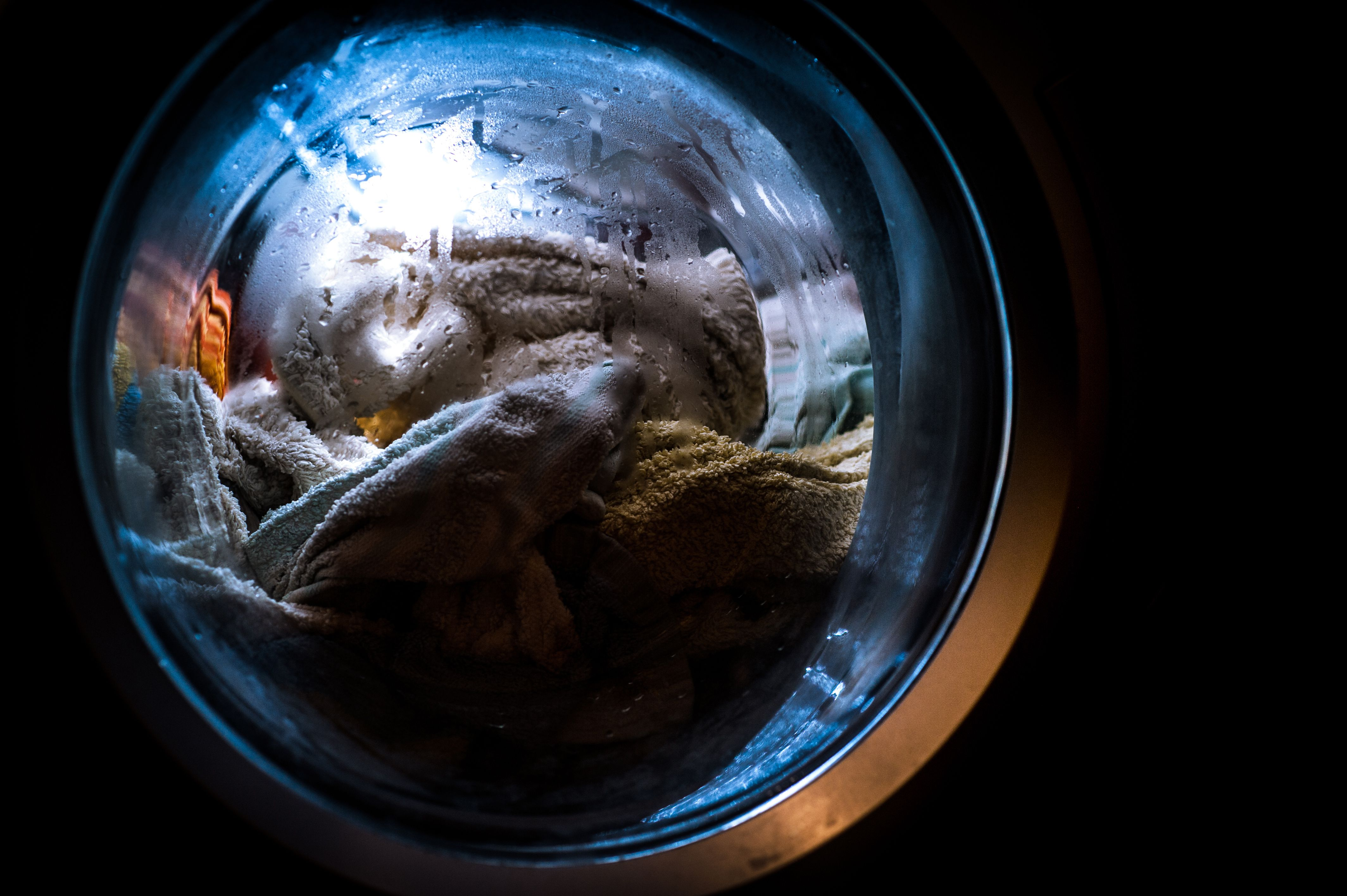 Close up of washing machine window full of wet clothes
