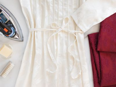 White damask dress next to red damask folded fabric next to clothing iron and cleaning materials