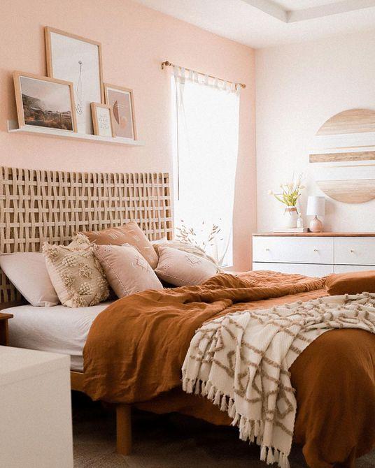 Habitación con paredes rosas y colchas anaranjadas
