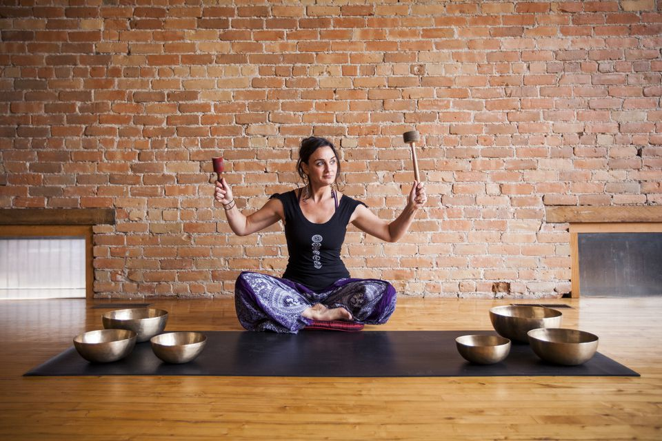 A meditation teacher uses singing bowls to create calmness