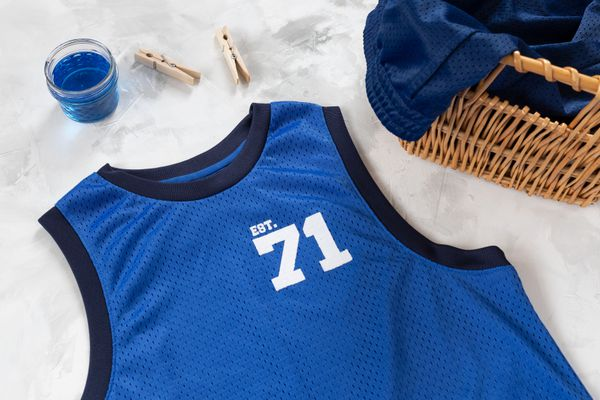 Blue basketball jersey next to laundry detergent, clothespins and basket of basketball shorts