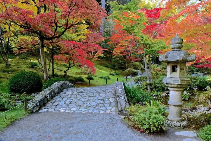 Stone path and stone temple sculpture in garden with red Japanese maples.