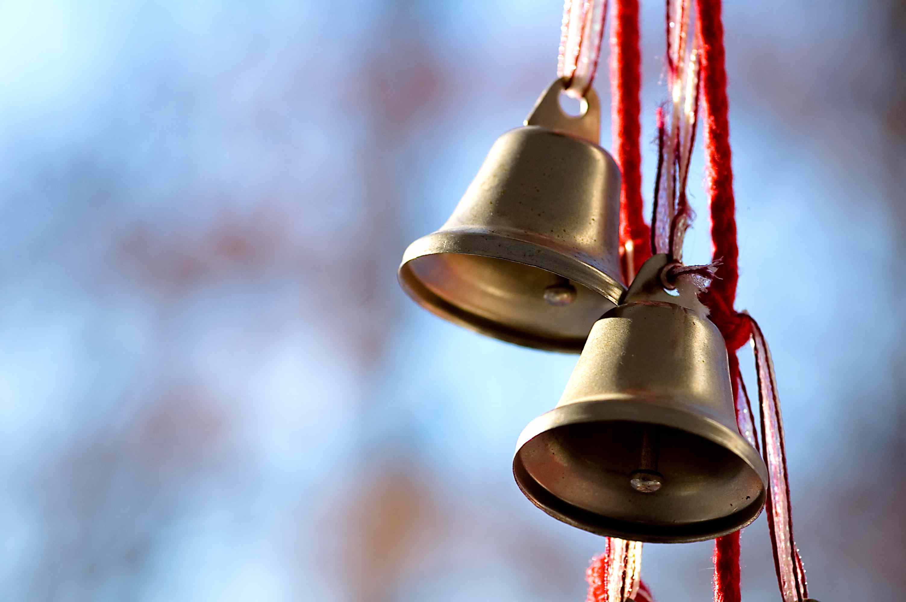 two metal bells hanging on a red ribbon and cord