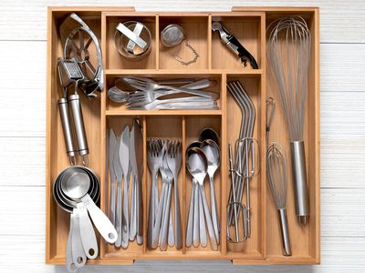 Stainless steel flatware in wooden organizer tray closeup