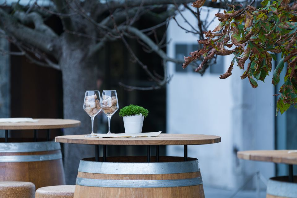 An outdoor wooden dining table with two glasses and a small potted plant on it