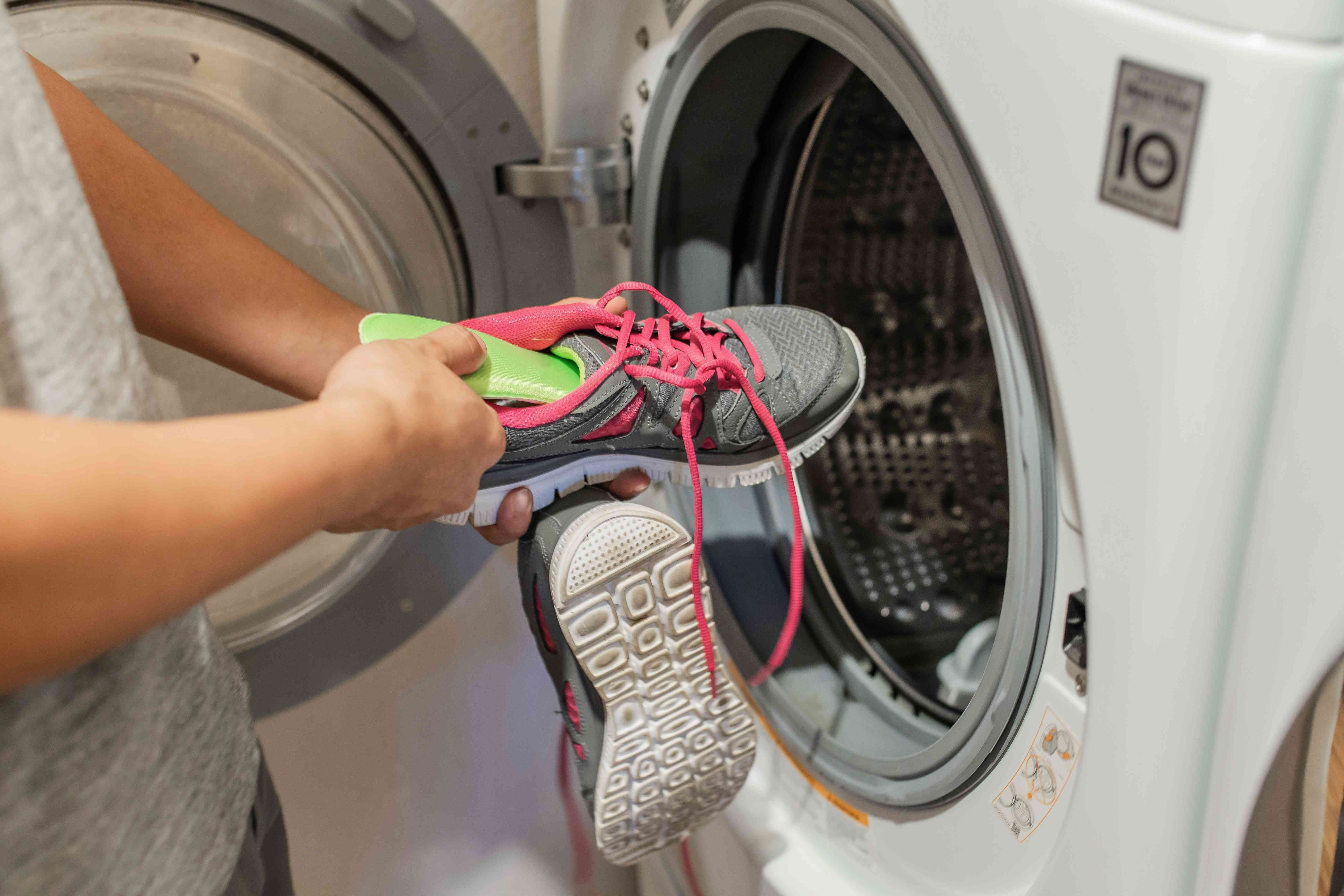 person tossing sneakers into the washer