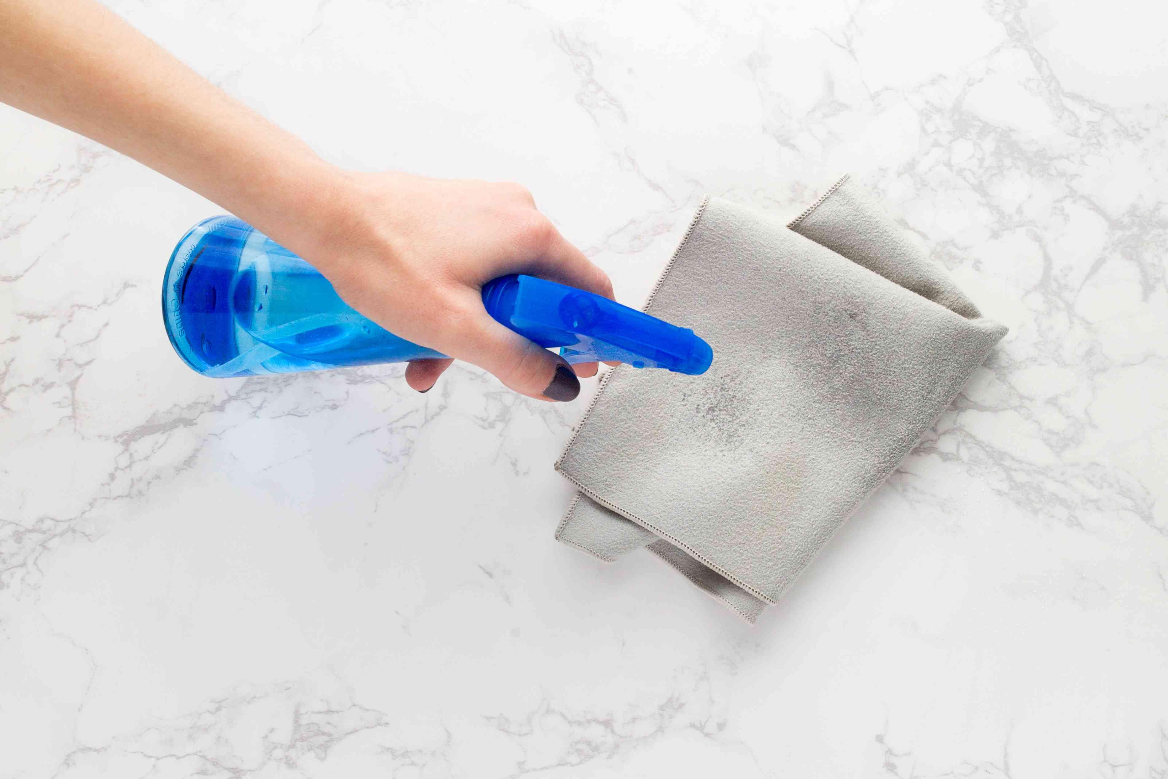 spraying a lint free microfiber cloth