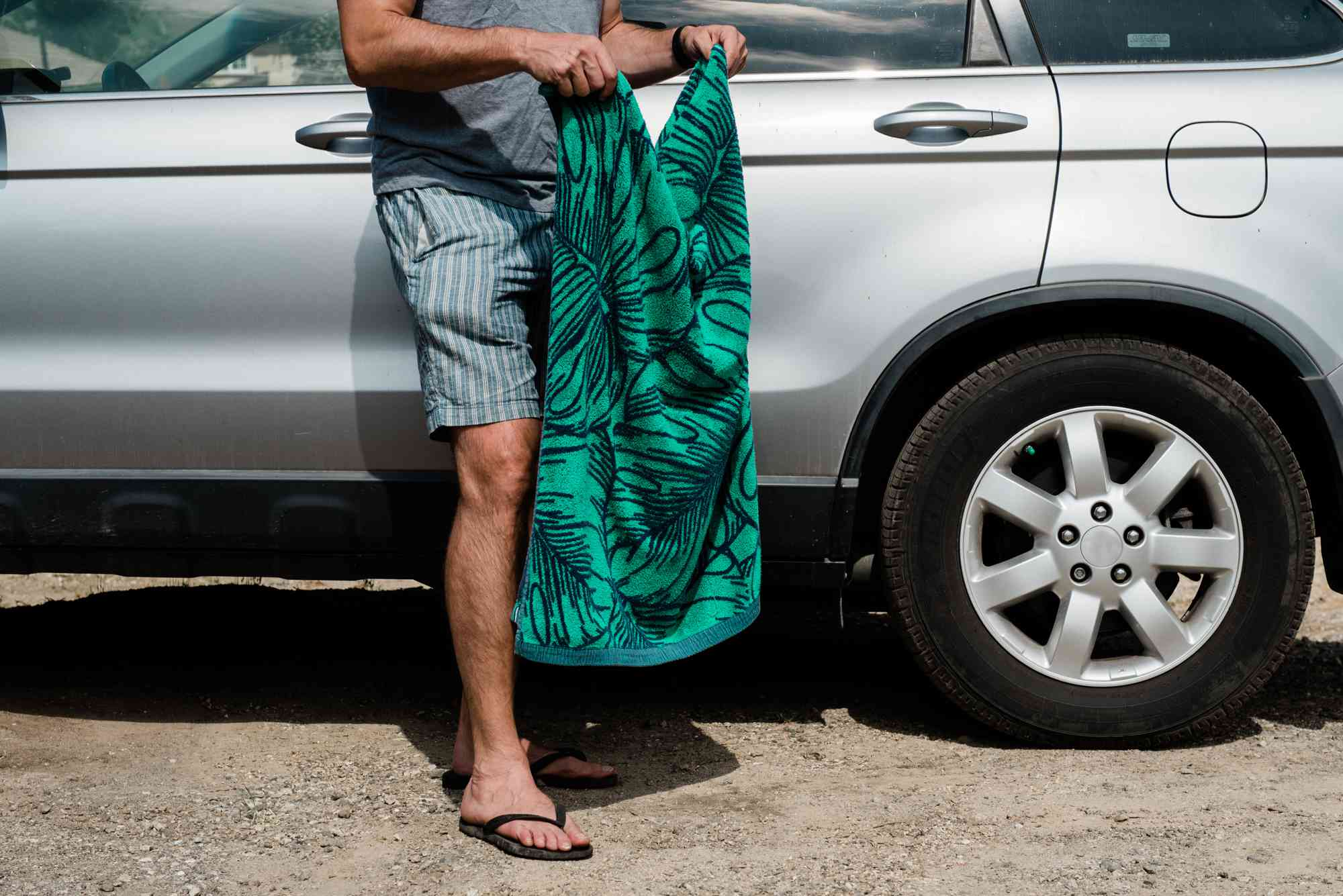 shaking out a sandy beach towel