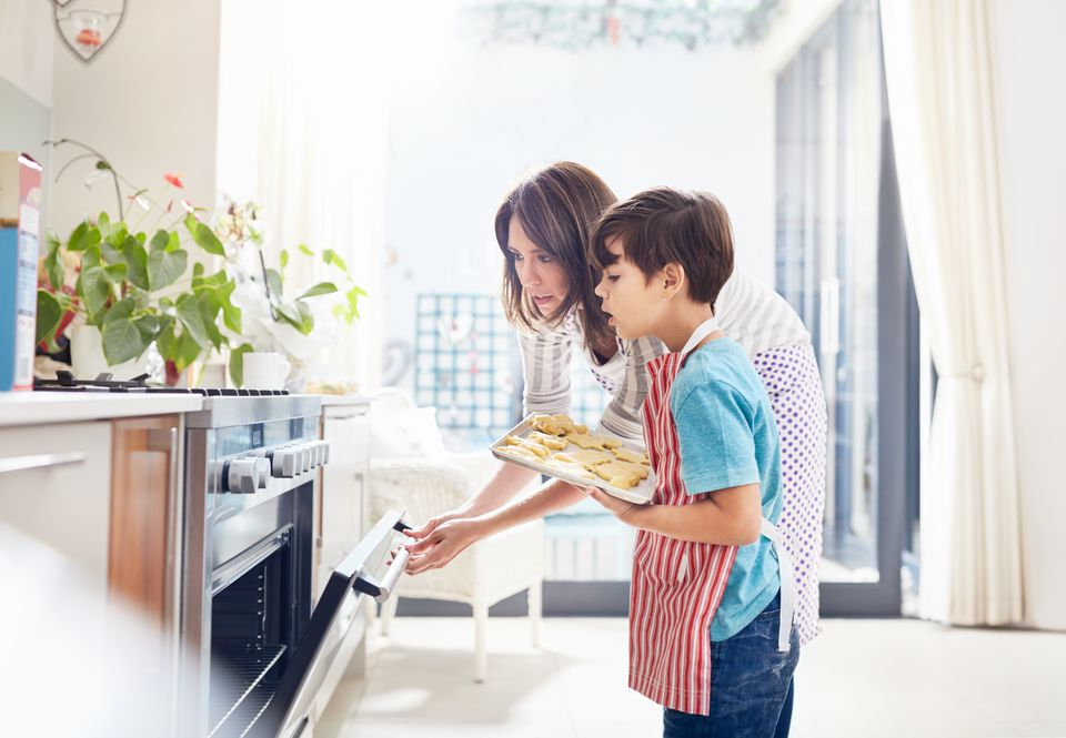 Mother and son baking, placing cookies in oven in kitchen