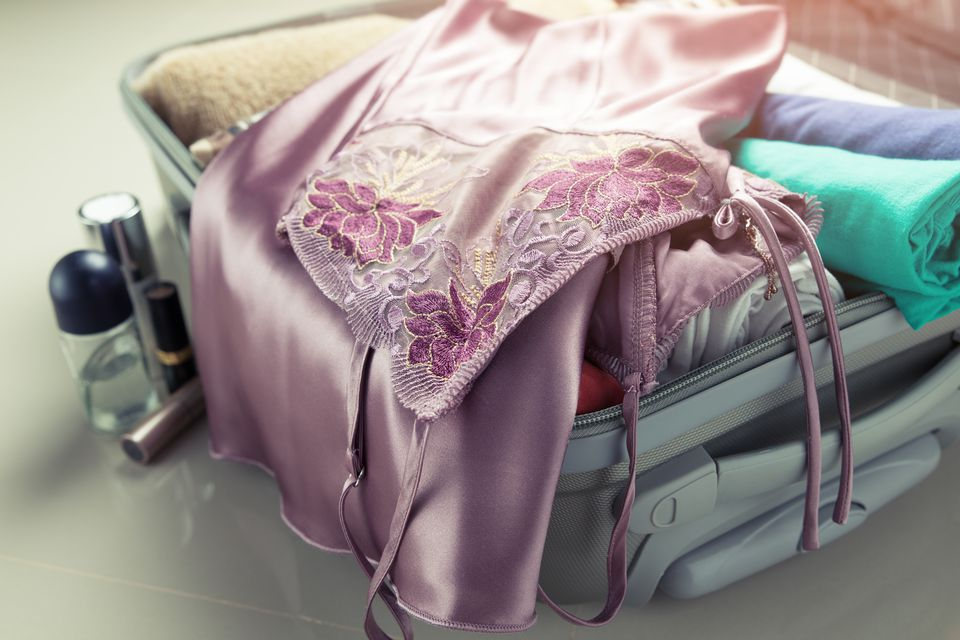 Close-up of pink nightie in suitcase on tiled floor