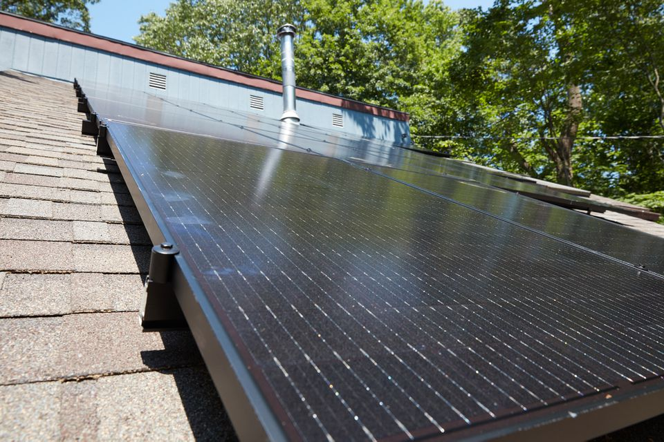 Black solar panels installed on brown roof tiles with trees in background