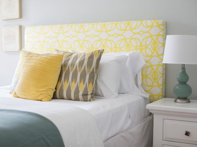 bed with white sheets and yellow headboard