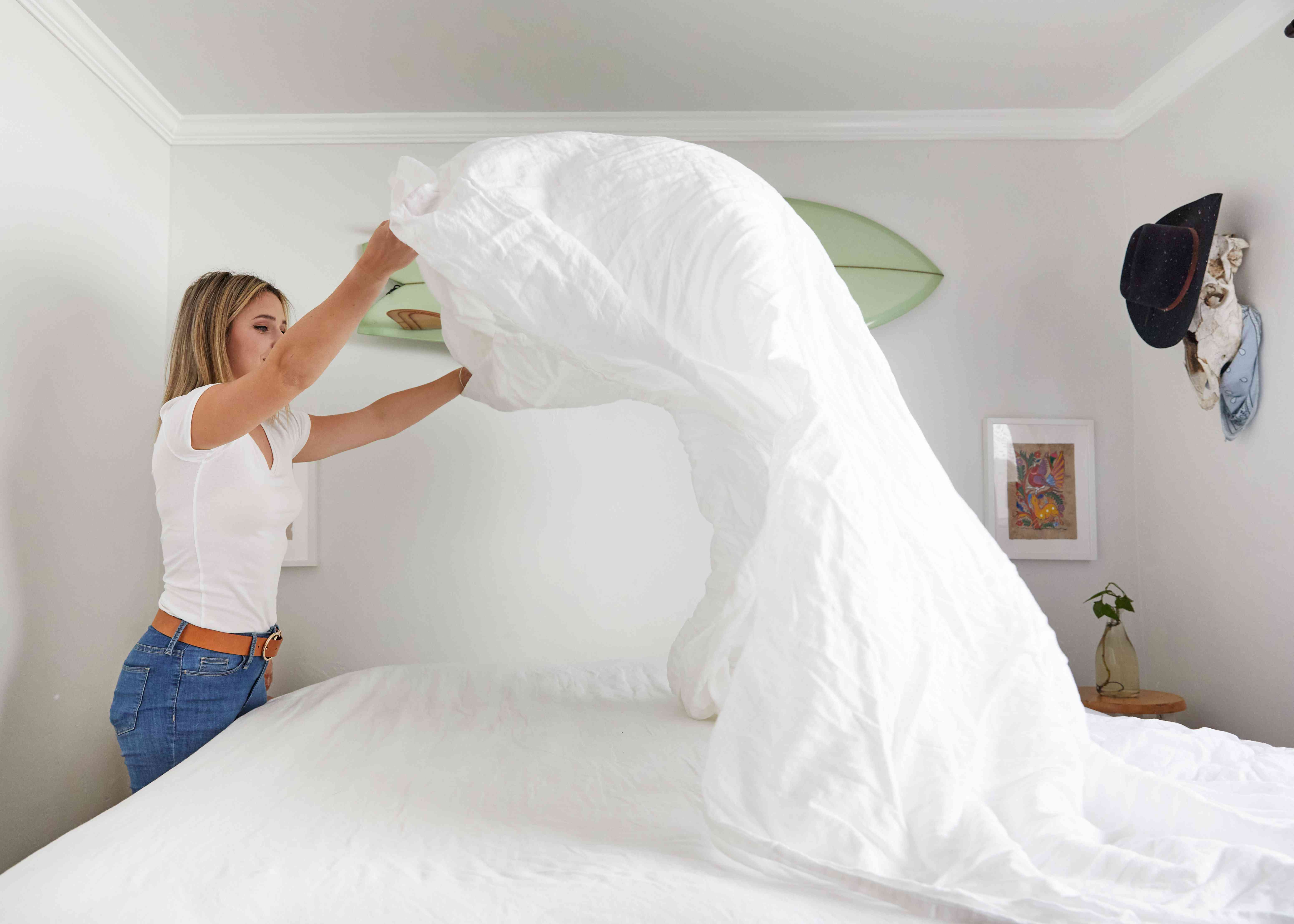 woman placing the top sheet on the bed