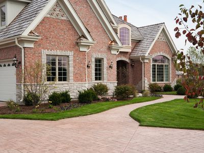 Lovely red brick upscale home with concrete driveway.