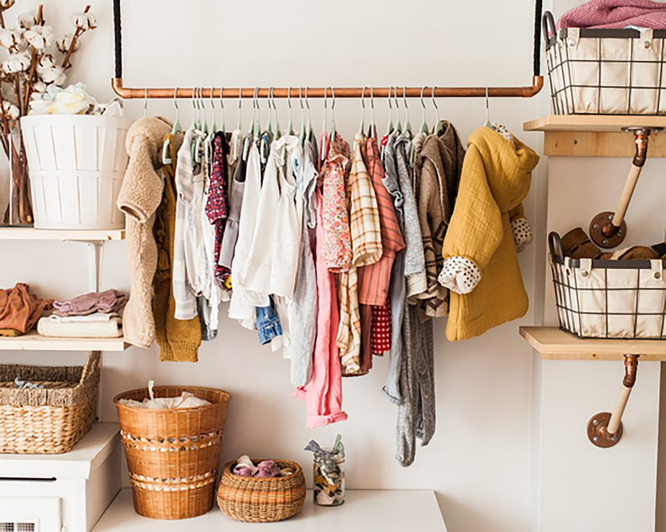 bedroom closet with baby clothes hanging up