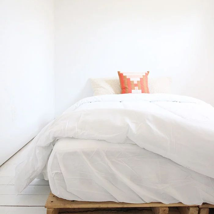 A pallet bed frame with white linens and a colorful pillow