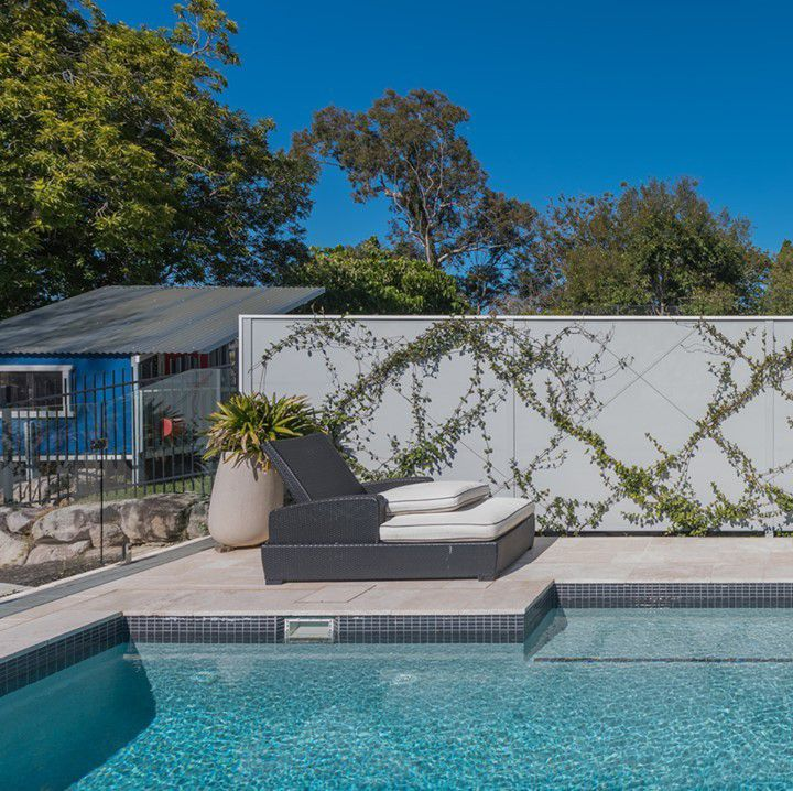 A pool surrounded by a modular wall with growing vines.