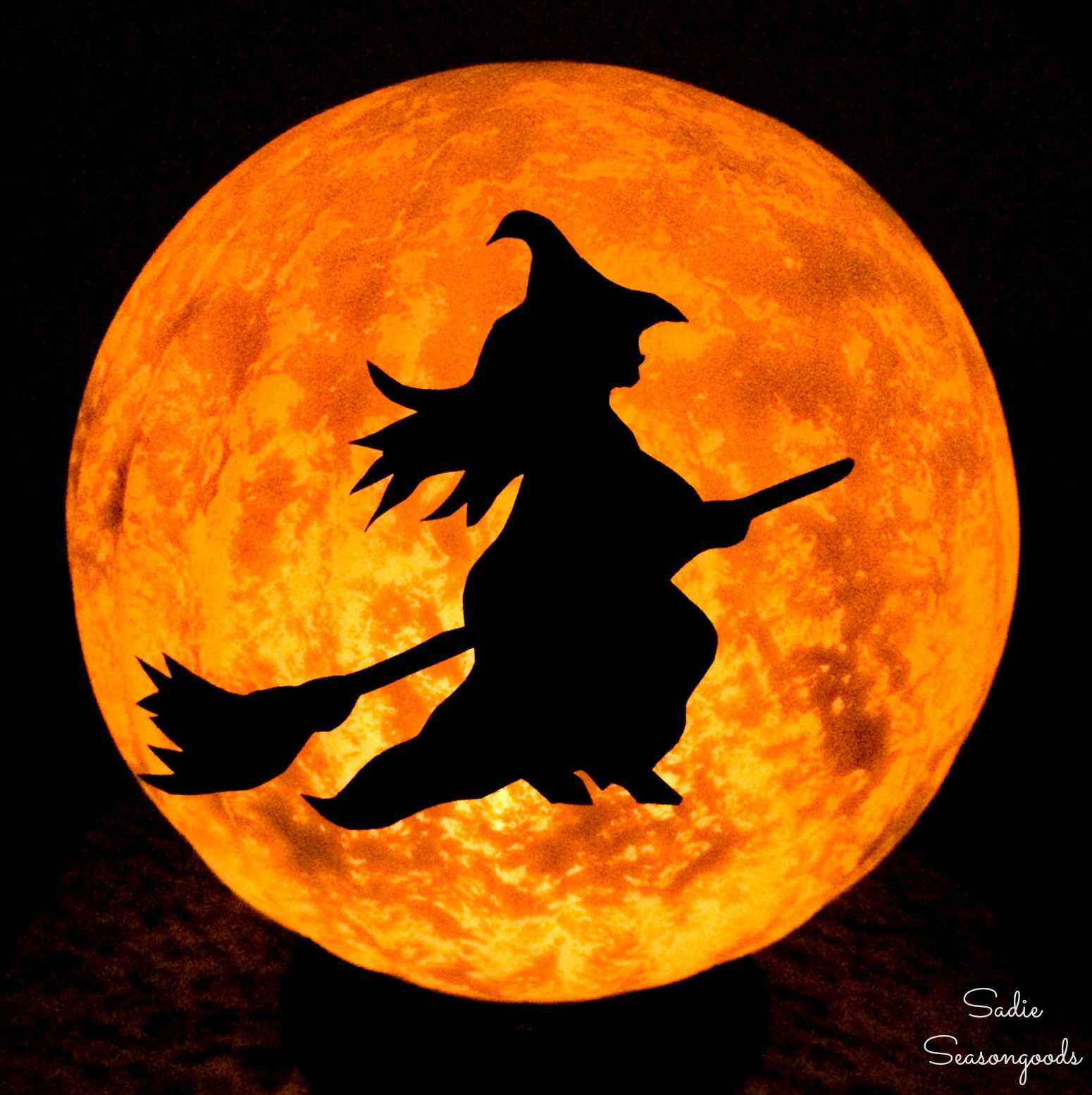 A witch riding a broomstick across the moon