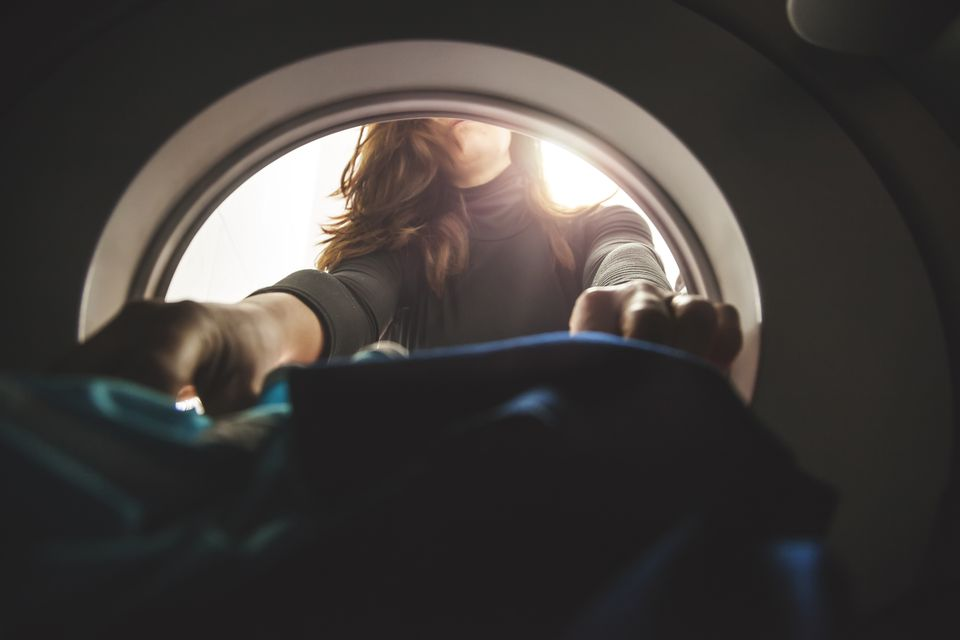 A woman putting clothes into the dryer from the machine's perspective