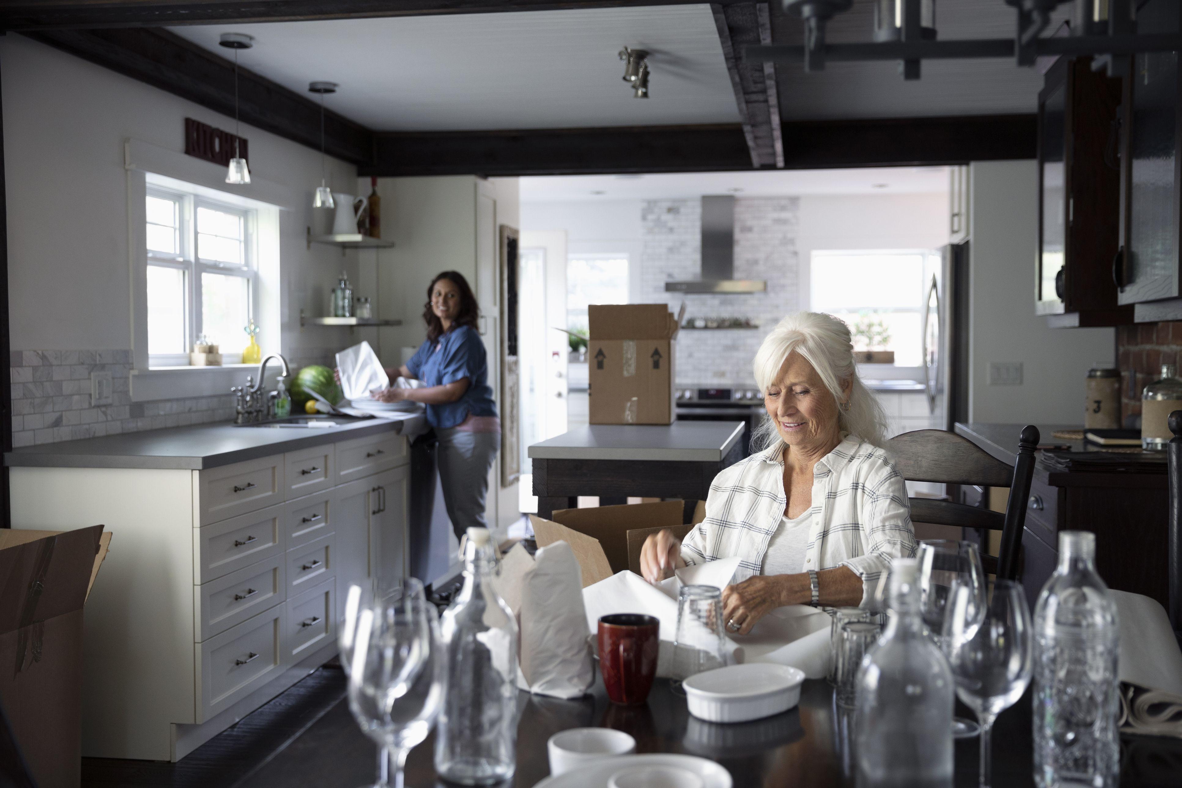 Senior woman downsizing, packing dishes